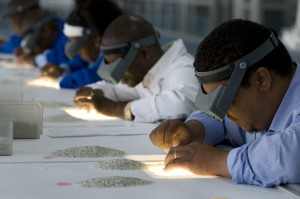 Workers sort and match pearls in the traditional manner.
